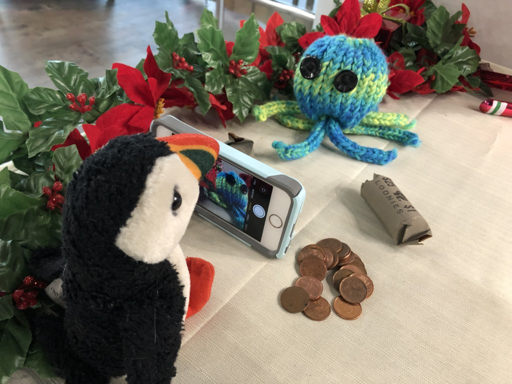 Puffy the puffin taking a picture of Brainy the octopus
