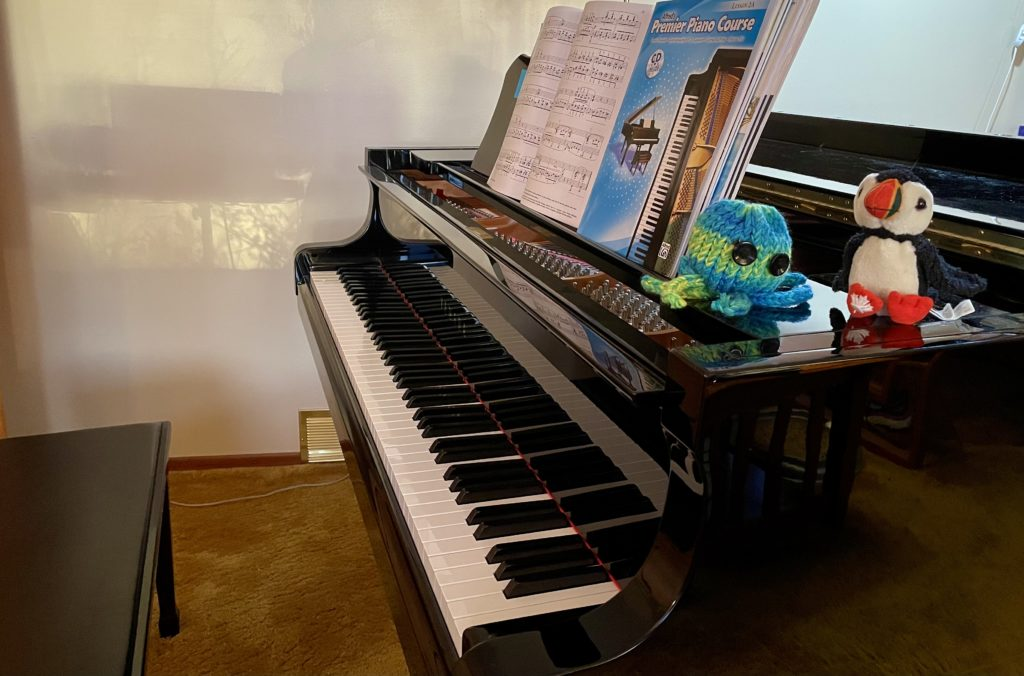 A piano with music books and two small stuffed animals
